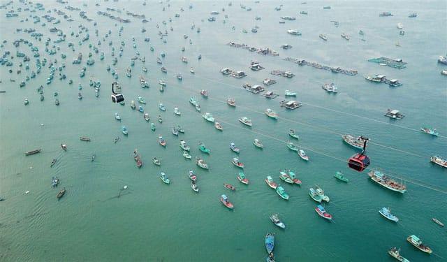 Những chiếc tàu đánh cá đầy màu sắc trên mặt biển xanh.